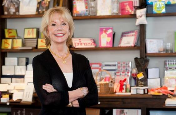 Maureen Hall smiling in front of shelves of stationery