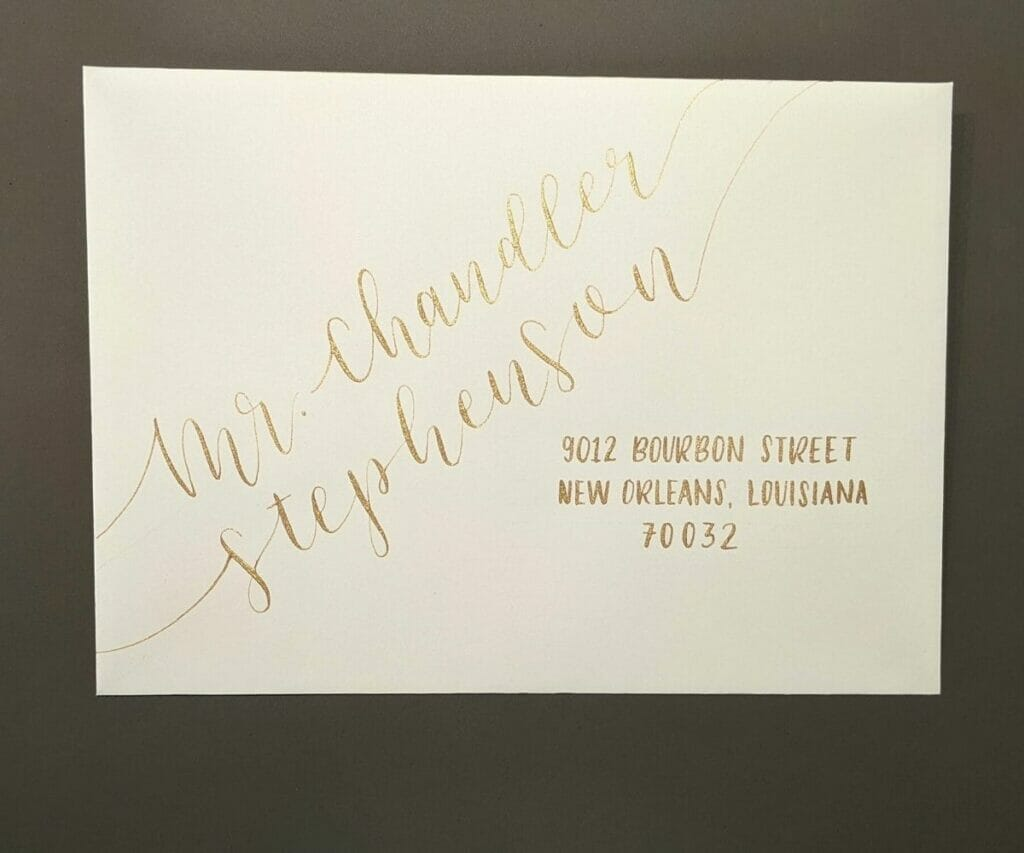 Gold calligraphy on envelope with name written diagonally in large, script font