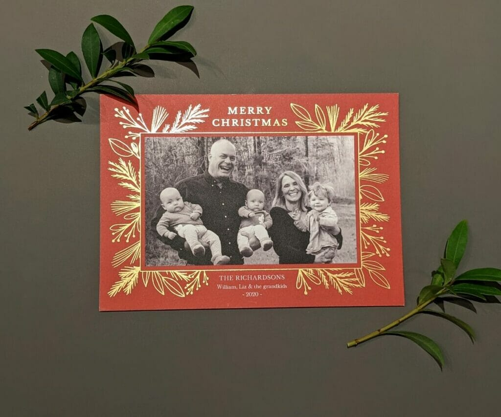 black and white photo holiday card with red border and gold embossed Merry Christmas and holiday greenery around it