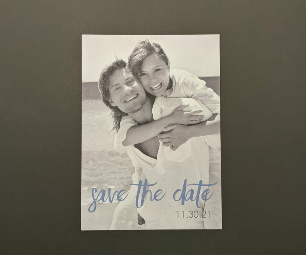 Clean, simple save the date card with black and white photo of the couple as the background