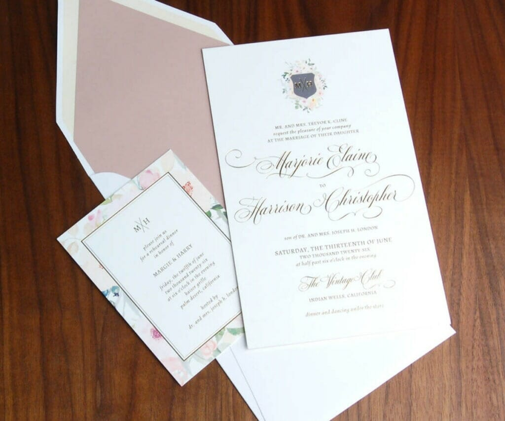 Wedding invitation with crest of couples initials surrounded by a small floral border on top and matching rehearsal dinner invitation and pink-lined envelopes