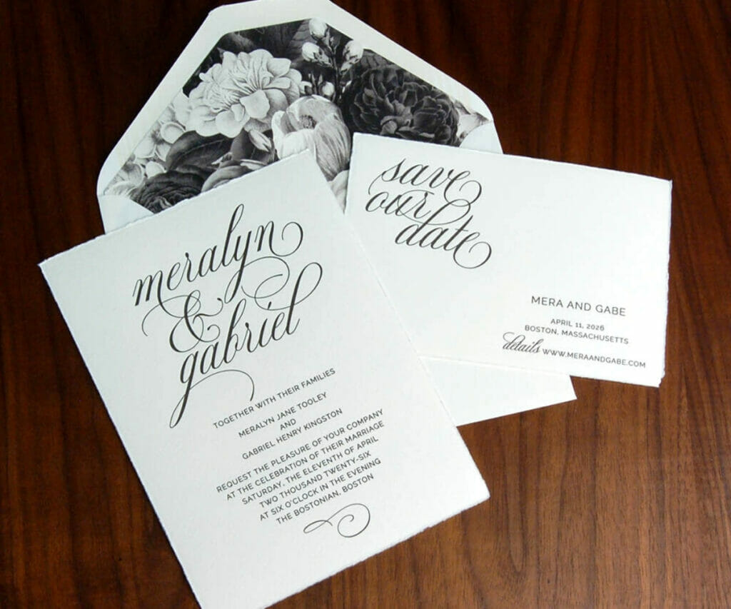 Elegant wedding invitations in black script on white card stock and a white envelope with black and white floral liner