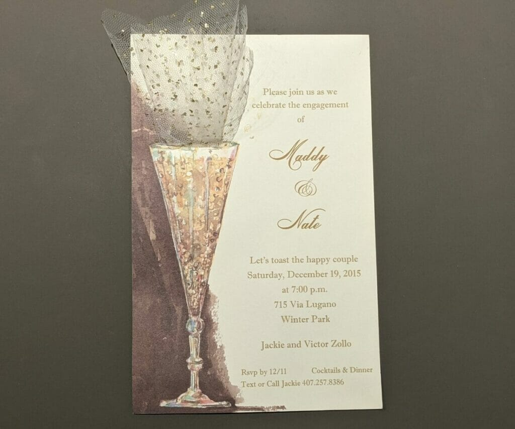 Fancy Engagement Party Invitation with elegant cocktail glass on the left hand side and glittery netting glued to top of glass