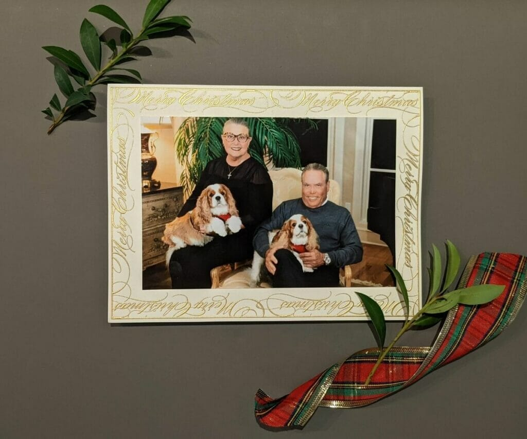 Photo holiday card of older couple and their two dogs with Merry Christmas in gold script as the border