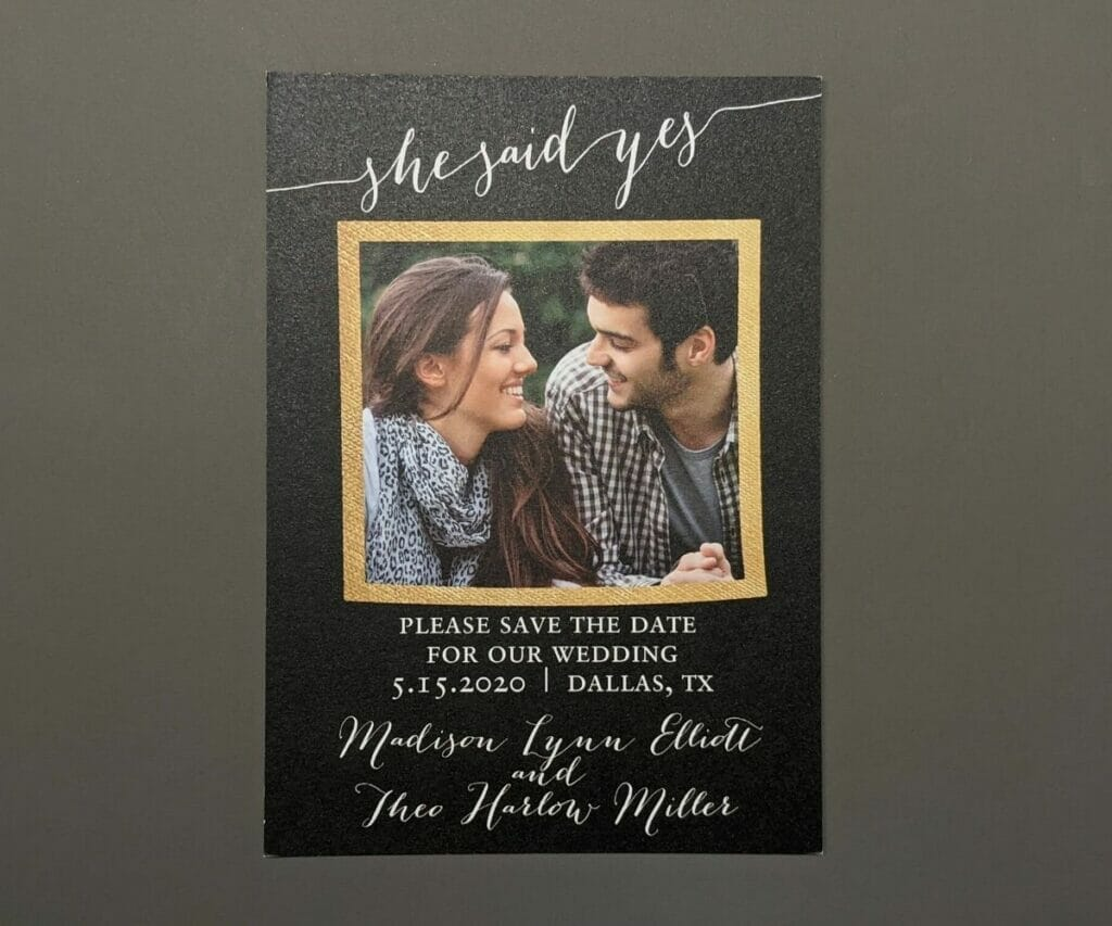Cute save the date card on black textured paper with a square photo of the couple in the middle