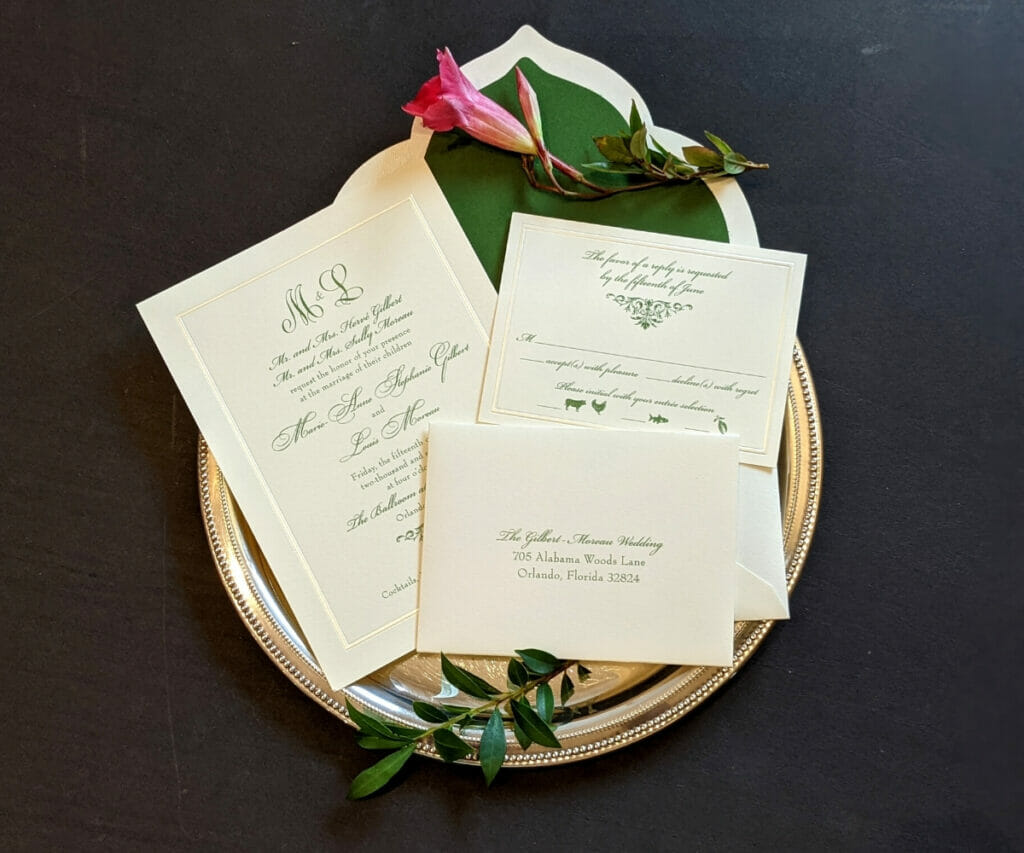 Classic wedding invitation, RSVP card, and matching envelope with green liner and scalloped flap on cream colored cardstock with green ink