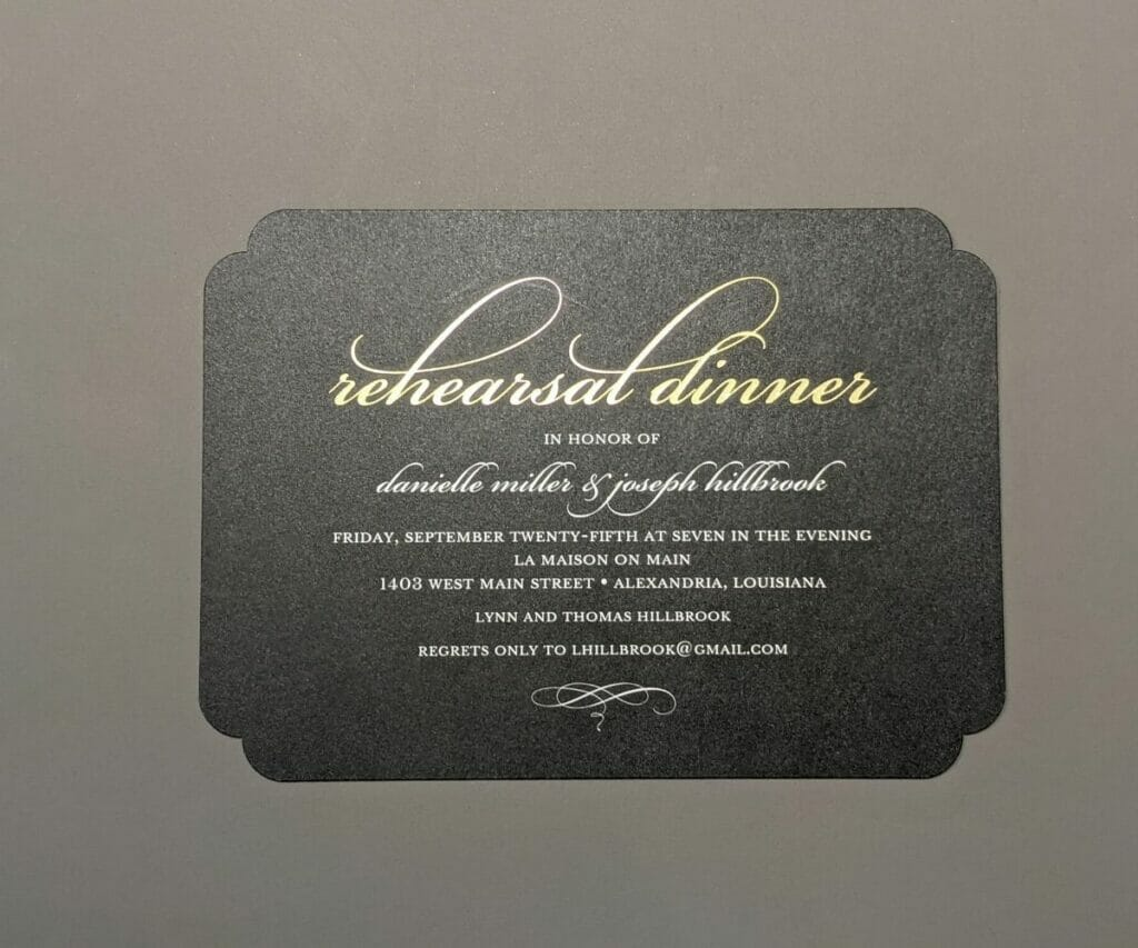 Elegant rehearsal dinner invitation on black textured paper with gold and silver script font and a small embellishment at the bottom