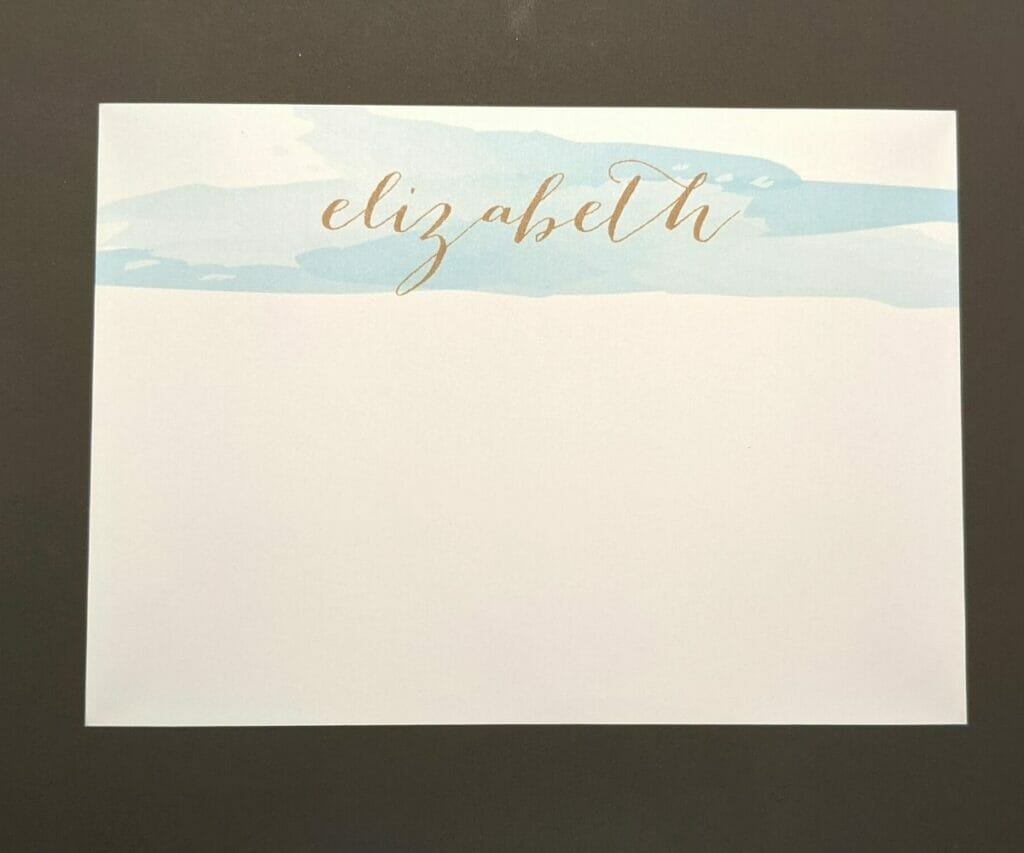 Elegant personalized stationery with gold embossed name at top on blue watercolor streak