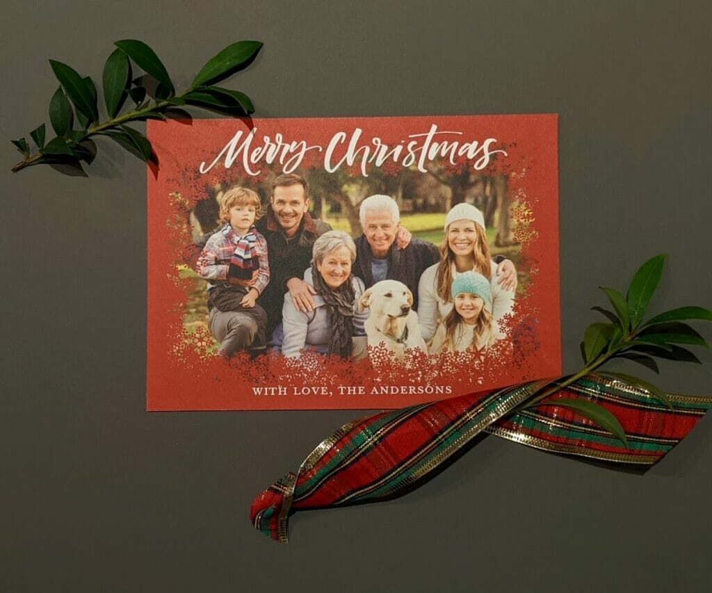 Photo Christmas card with red snowflake border around the photo of the family