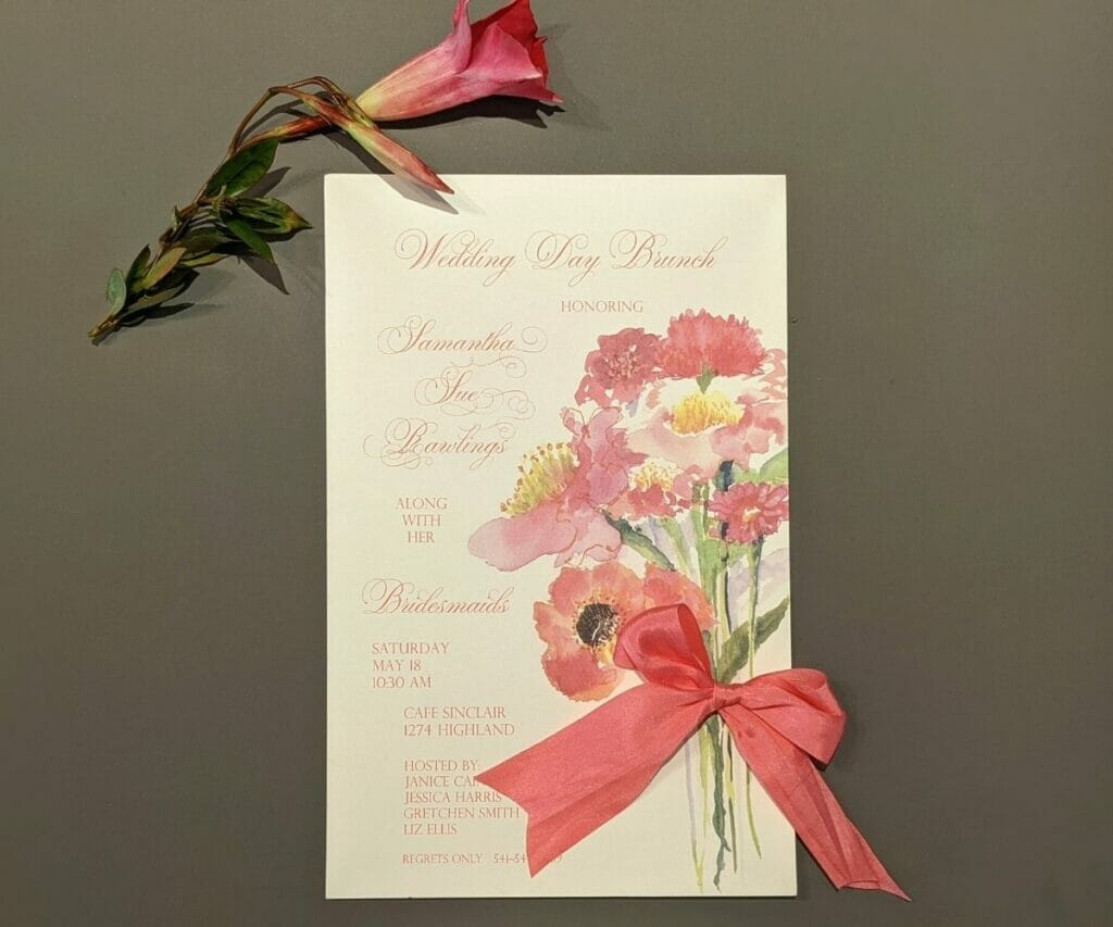 Wedding Day Brunch Invitation with long-stemmed pink flowers printed on the right side with a fabric ribbon tied into a bow in the center of the stems