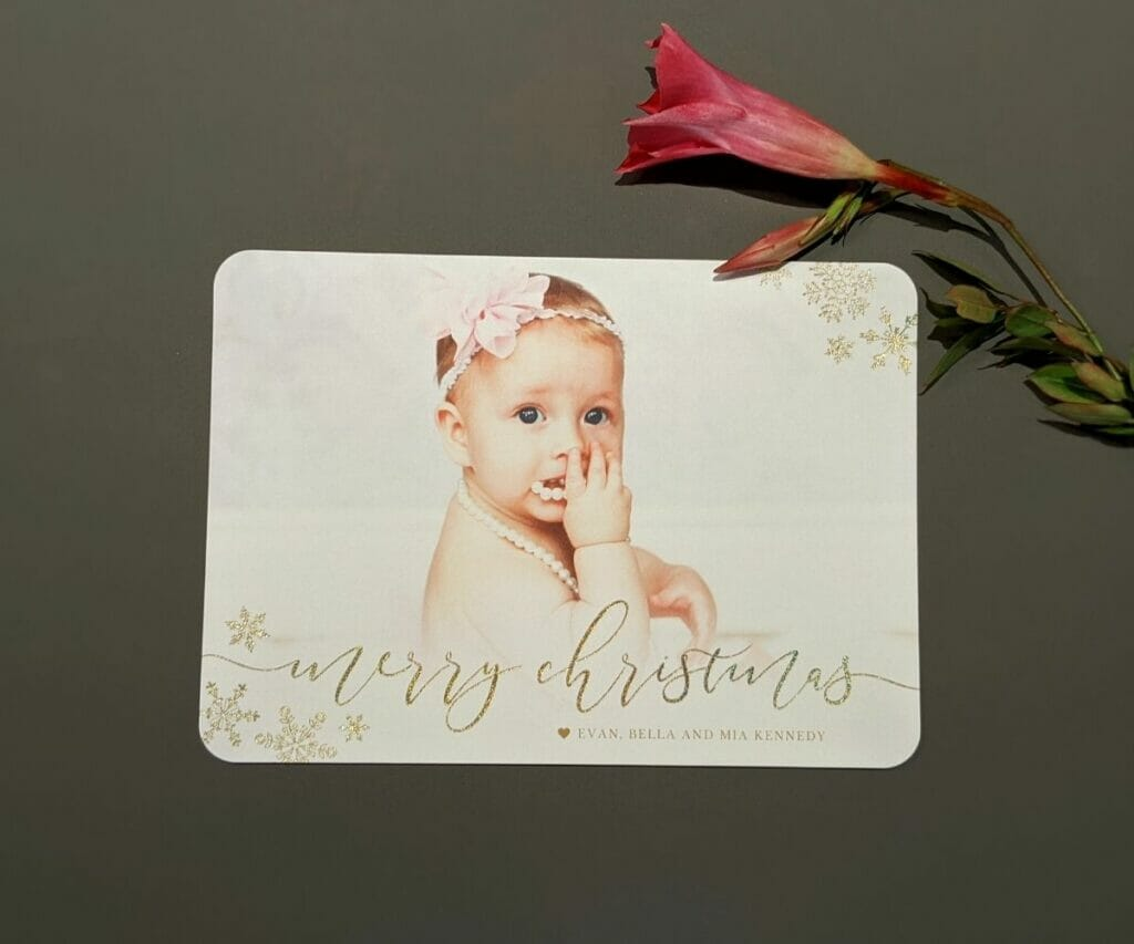 Merry Christmas holiday card with elegant silver snowflakes in two corners and a baby on the front