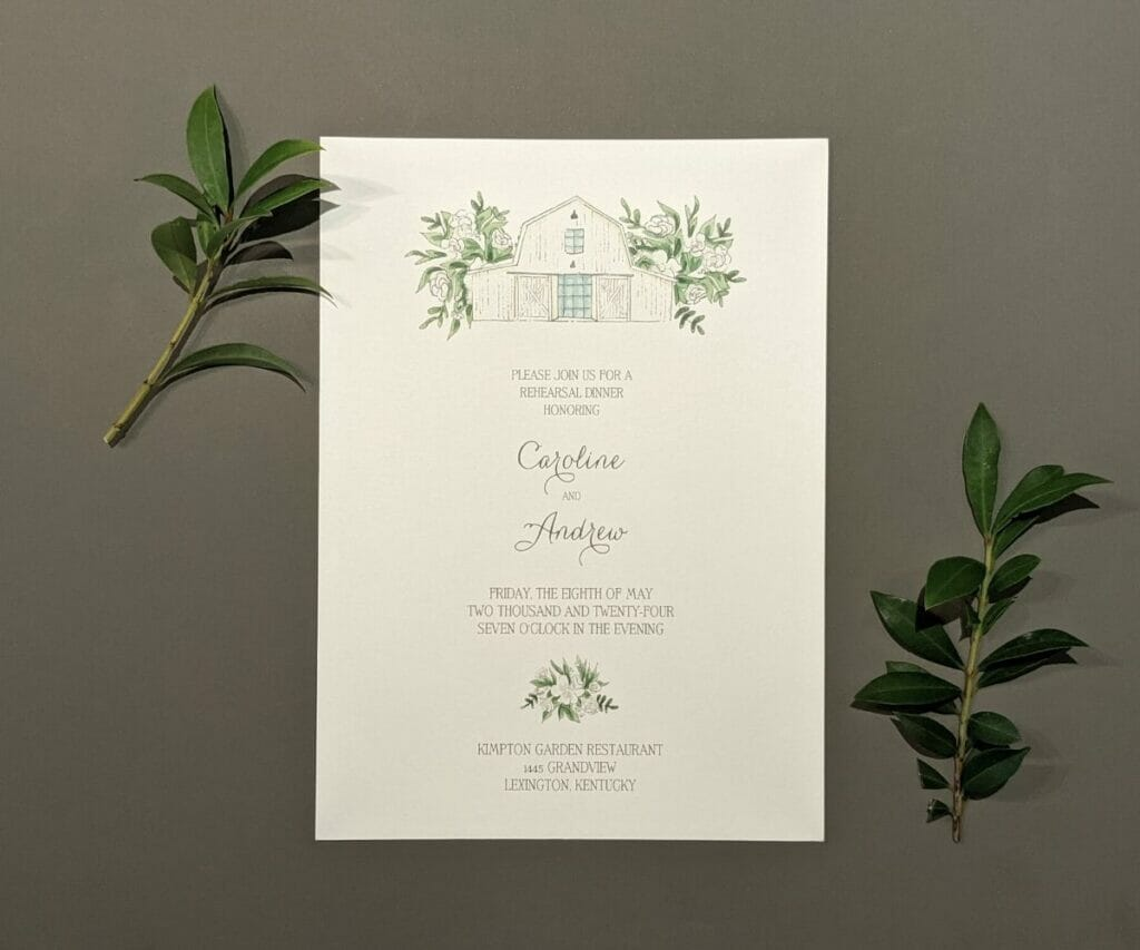 Classically simple wedding invitation with a pencil drawing of a barn framed by two-toned floral spray at the top and a small floral spray at the bottom
