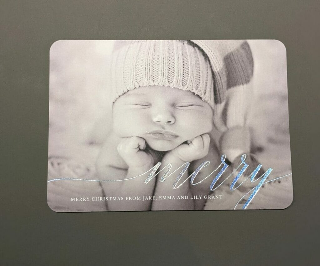 "Black and white holiday card with newborn baby and ""Merry"" on it"