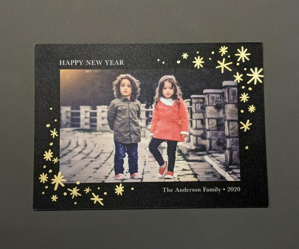 Happy New Year Holiday Card with black textured cardstock and gold stars around pictures of two cute kids