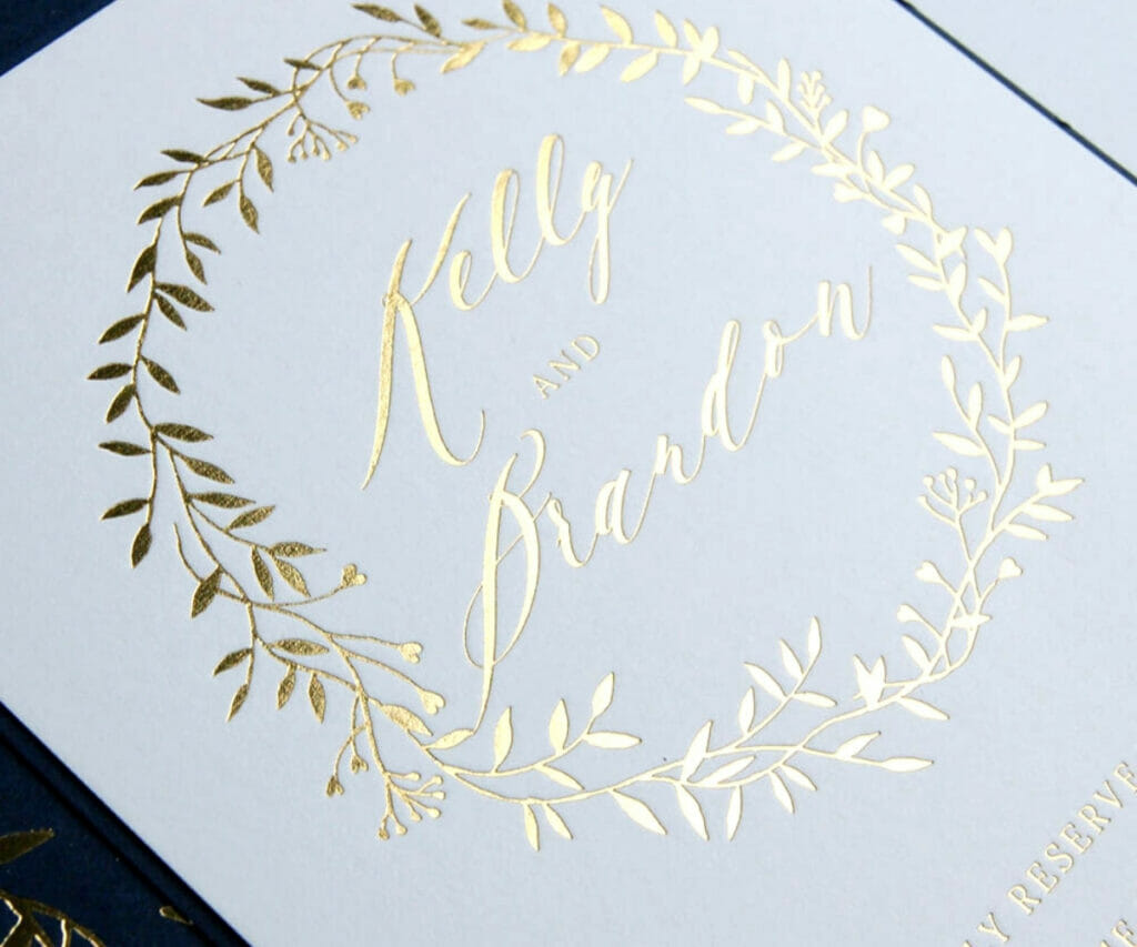 Gold embossed vine circling a couple's name on a wedding invitation