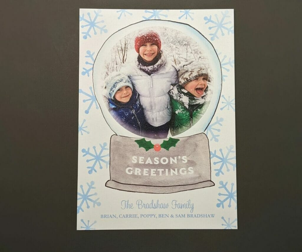 Cute photo Christmas card with large blue snowflakes and picture of three boys framed in a snow globe