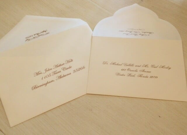 Two envelopes with black calligraphy script addresses, one with a scalloped flap