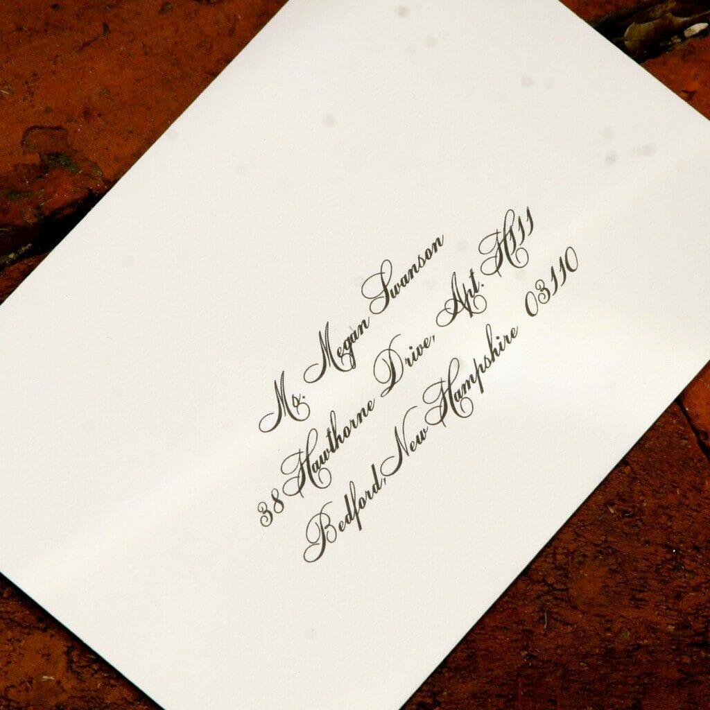 Black calligraphy address on white envelope
