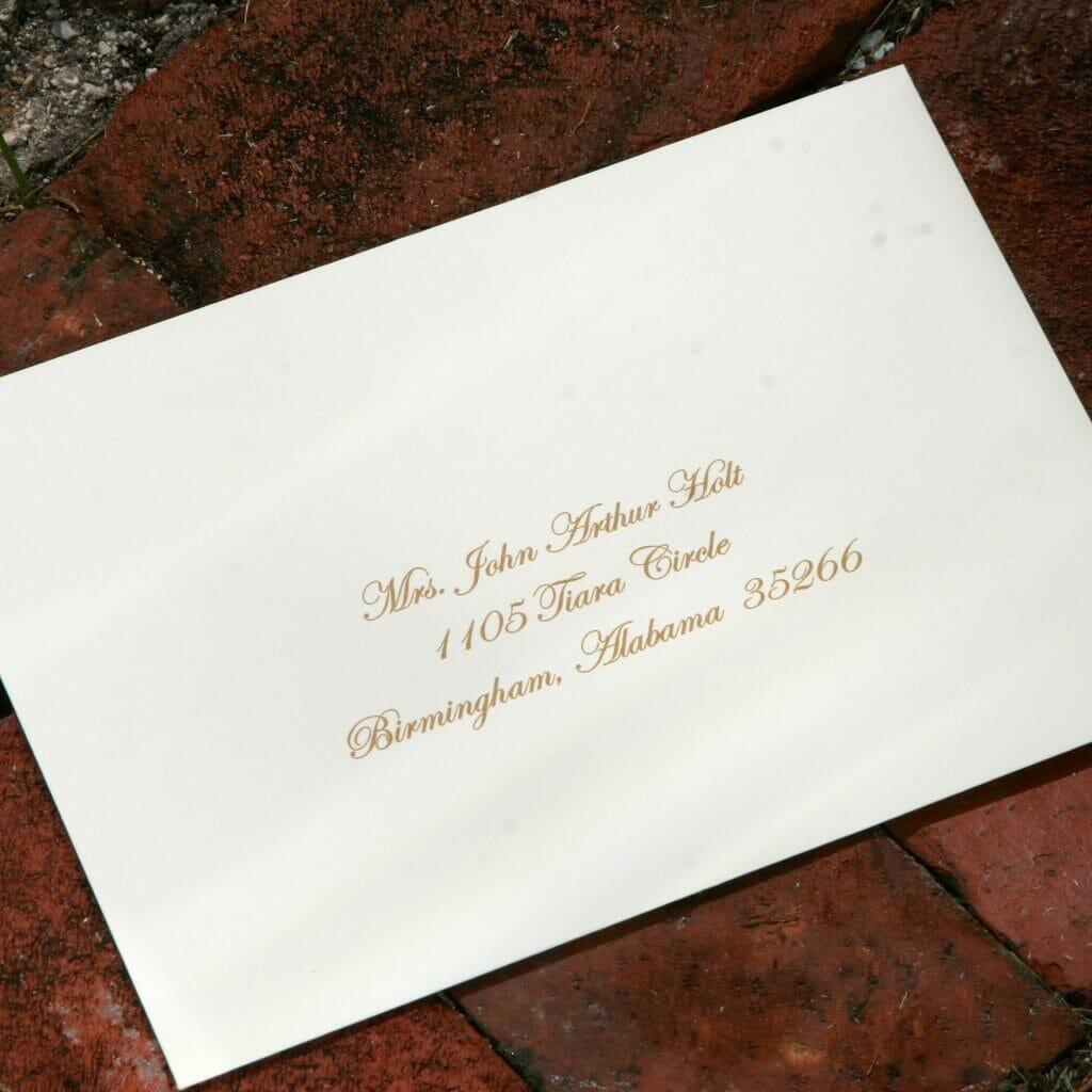 Gold script calligraphy on white envelope